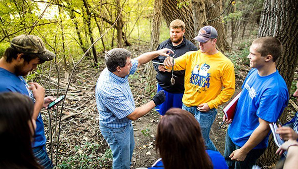 A professor and students conducting research in a forest