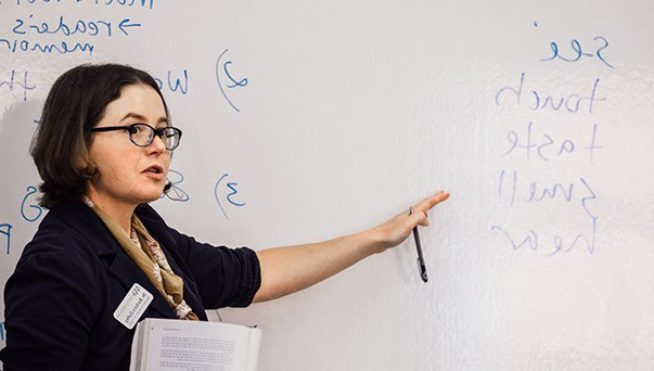 A professor pointing at a whiteboard
